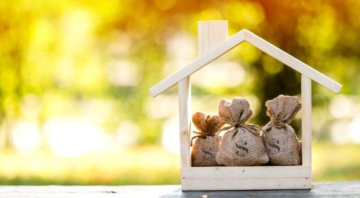 a wooden house shape holds 3 bags of cash representing reits to buy