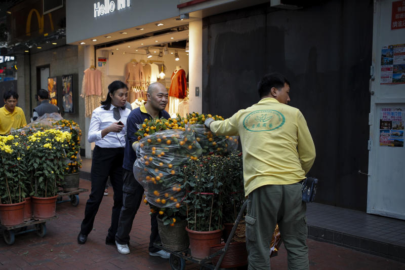 Workers push carts loaded with mandarin orange plants and flowers to their customer passing by a closed shop lot covered with steel panel in Hong Kong, Saturday, Jan. 4, 2020. City's businesses has been hit badly following the months-long pro-democracy movement has extended into 2020 with further mass demonstrations. (AP Photo/Andy Wong)