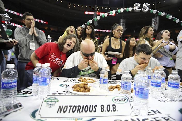 "Bob ""Notorious B.O.B."" Shoudt, left, takes part in the Wing Bowl on Friday, Feb. 3, 2017 in Philadelphia. Shoudt choked down 409 chicken wings to become the finger-licking champion of Philadelphia's Wing Bowl. The morning eating ordeal draws boozy spectators who tailgate beforehand outside the city's sports arena to watch flamboyant contestants and suggestively-clad women known as Wingettes. This year, rapper Coolio performed between rounds. (David Swanson/The Philadelphia Inquirer via AP)"