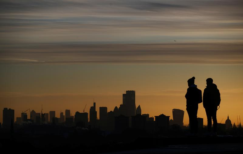 People watch the sun rise behind the city of London financial district and The Shard in London, Britain, December 11, 2019. REUTERS/Hannah McKay