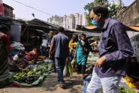 People wearing face mask as a precautionary measure against the coronavirus buy vegetables inside a narrow alley in Kolkata, India, Sunday, Nov. 22, 2020. (AP Photo/Bikas Das)