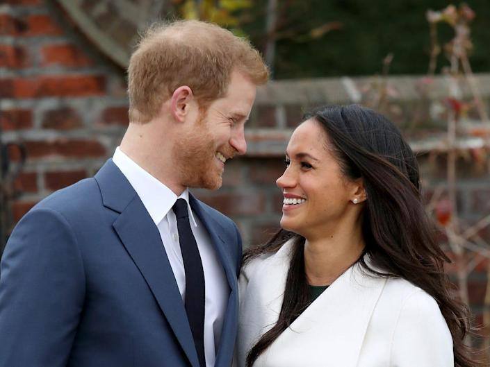 Prince Harry and Meghan Markle smile at each other as they announce their engagement.