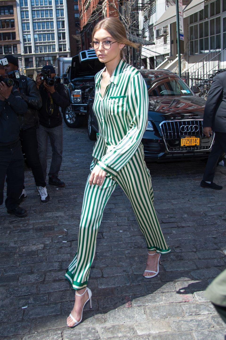 <p>In personally monogrammed green striped silk pajamas by Morgan Lane with white Stuart Weitzman sandals and clear round glasses while leaving her apartment in NYC. </p>
