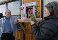 In this Thursday, Dec. 6, 2012, photo, Rick Brooks, left, and artist Elizabeth Kennedy pose beside one of the Little Free Libraries lending boxes, in Hudson, Wis. The non-profit Little Free Libraries movement is branching out in new directions including inner-city neighborhoods where kids might not have many books and into developing countries were people are hungry for reading material and by Christmas expects its followers will have erected over 5,000 book boxes across the U.S. alone. Brooks is co-founder of Little Free Libraries. (AP Photo/Jim Mone)