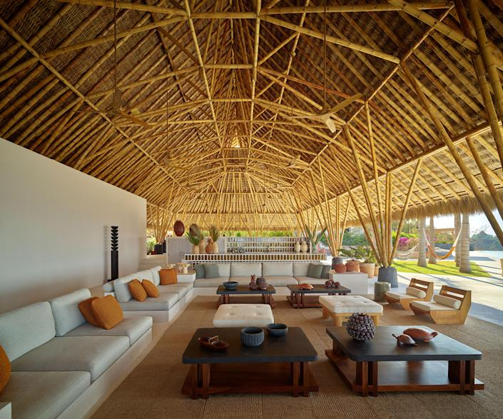custom sofas in a Pierre Frey fabric line the bamboo-canopied Palapa living room. Laplace designed the Parota-wood-and-lava-stone cocktail tables. René Martin lounge chairs; Karl Springer ottomans.