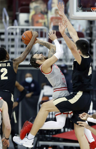Ohio State guard Duane Washington, center, goes up for a shot between Purdue guard Eric Hunter, left, and center Zach Edey during the first half of an NCAA college basketball game in Columbus, Ohio, Tuesday, Jan. 19, 2021. (AP Photo/Paul Vernon)