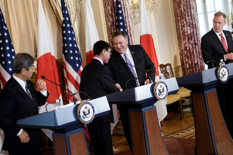 Secretary of State Mike Pompeo shakes hands with Japanese Foreign Minister Taro Kono as the allies' defense chiefs look on