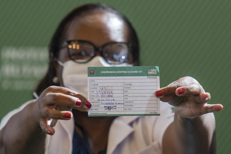 Nurse Monica Calazans, 54, shows her vaccination card after being the first Brazilian to receive the COVID-19 vaccine produced by China's Sinovac Biotech Ltd, at the Hospital das Clinicas in Sao Paulo, Brazil, Sunday, Jan. 17, 2021. (AP Photo/Carla Carniel)