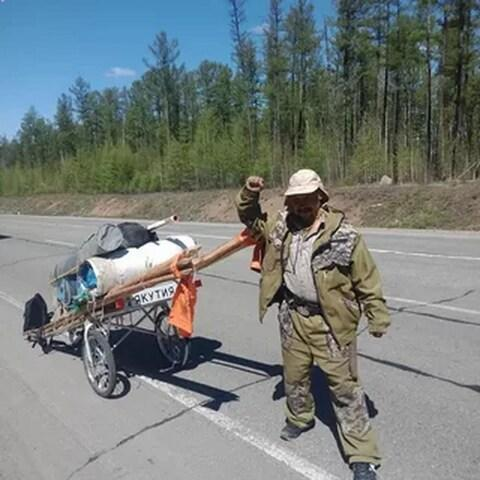 Mr Gabyshev carries a yurt and stove in his pull-cart - Credit: VK