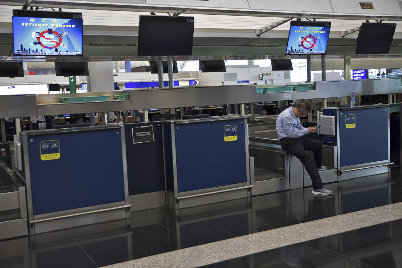 A man browses his smartphone at the empty check-in counters in the departure hall of the Hong Kong International Airport in Hong Kong, Tuesday, Aug. 13, 2019. (Photo: Vincent Thian/AP)