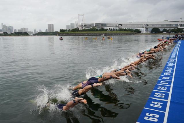 """FILE - In this Aug. 15, 2019, file photo, athletes dive into the water at the start line during a women's triathlon test event at Odaiba Marine Park, a venue for marathon swimming and triathlon at the Tokyo 2020 Olympics, in Tokyo. The IOC moved next year's Tokyo Olympic marathons and race walks out of the Japanese capital to avoid the stifling heat and humidity. Some swimmers and an 11,000-member coaching body want similar treatment: find an alternative to the distance-swimming venue in Tokyo Bay known as the """"Odaiba Marine Park.""""(AP Photo/Jae C. Hong, File)"""