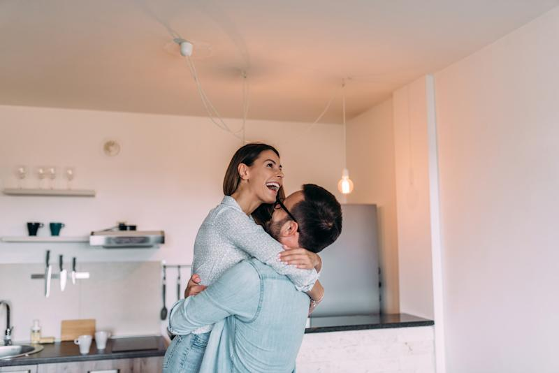 A man lifting a smiling woman in an embrace in a kitchen