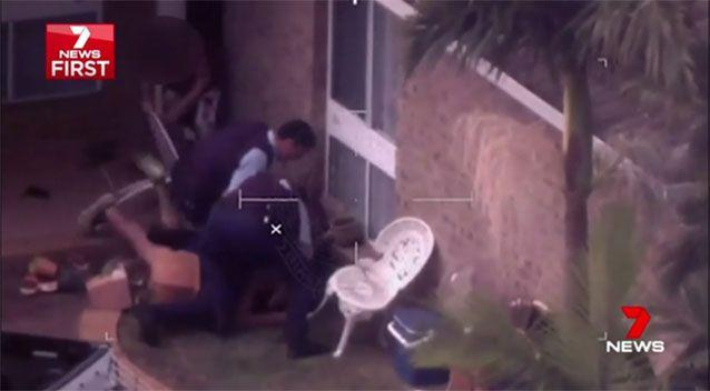 As he goes for the knife, it takes three officers and a burst of capsicum spray to bring him down. Picture: 7 News
