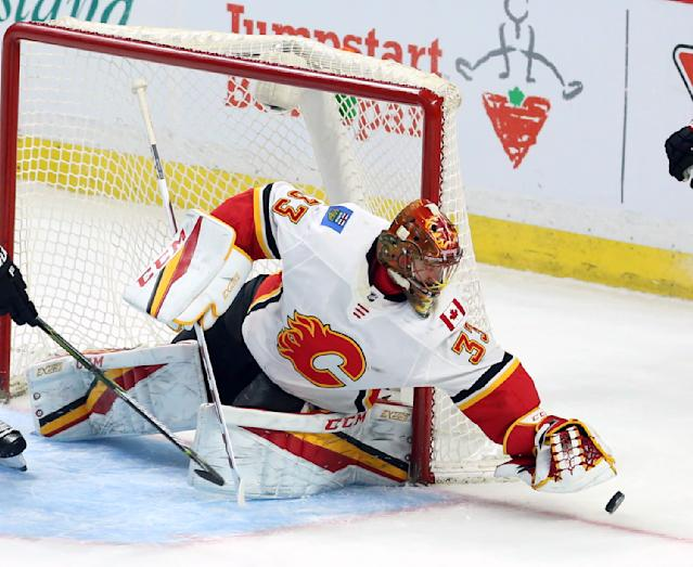 Calgary Flames goaltender David Rittich (33) reaches out to gain control of the puck during the second period of an NHL hockey game against the Ottawa Senators in Ottawa, Friday, March 9 2018. (Fred Chartrand/The Canadian Press via AP)
