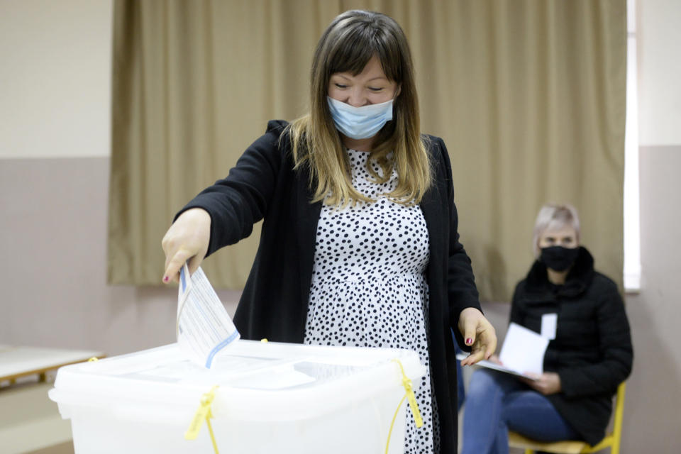 Irma Baralija casts her ballot for the local elections at a polling station in Mostar, Bosnia, Sunday, Dec. 20, 2020. Baralija hopes to win her race as the southern Bosnian city of Mostar holds its first local election in 12 years. (AP Photo/Kemal Softic)