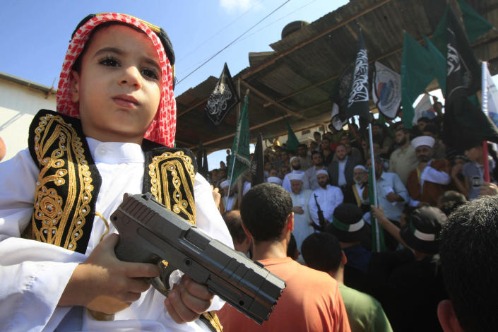 A boy holds a toy gun during a protest about a film ridiculing Islam's Prophet Muhammad in the Palestinian refugee camp of Ain el-Hilweh near Sidon, Lebanon, Friday, Sept. 14, 2012. (AP Photo/Mohammed Zaatari)