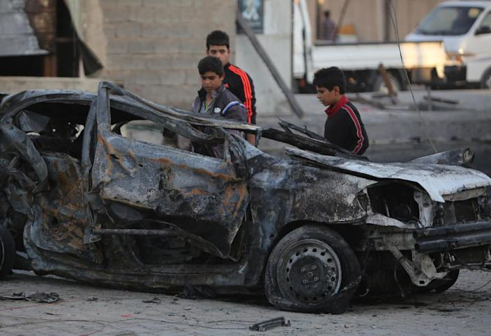 Iraqi children look at debris after a car bomb explosion that targeted the mostly Shiite Sadr City district of northeast Baghdad, on November 9, 2014 (AFP Photo/Ahmad al-Rubaye)