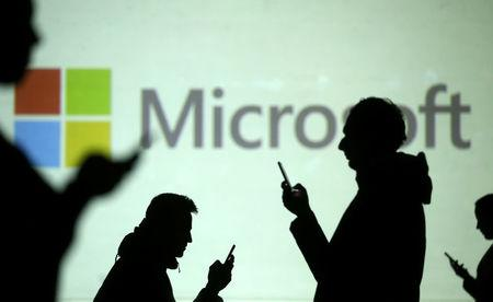 Silhouettes of mobile users are seen next to a screen projection of Microsoft logo in this picture illustration taken March 28, 2018.  REUTERS/Dado Ruvic/Illustration