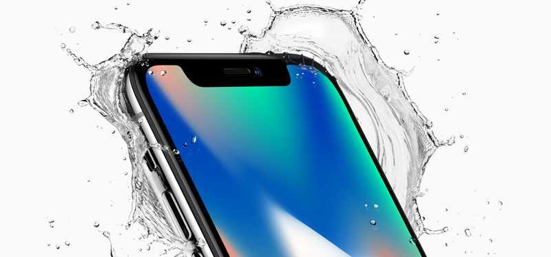 An iPhone X with water splashing around it.
