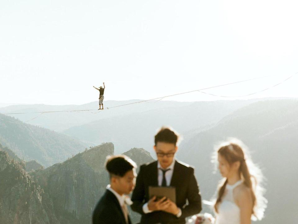 A person walks on a tightrope behind a couple getting married.