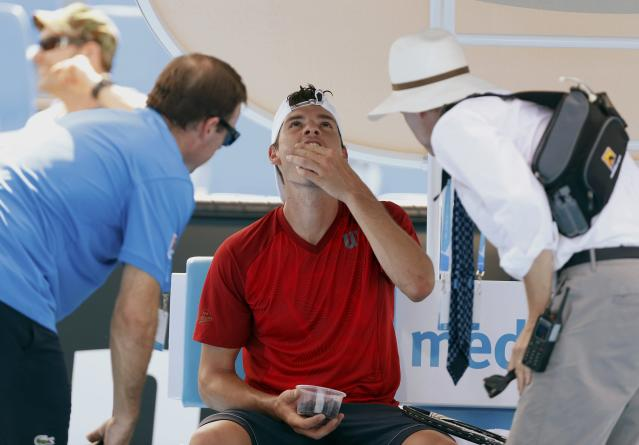 Frank Dancevic of Canada receives medical attention during his men's singles match against Benoit Paire of France at the Australian Open 2014 tennis tournament in Melbourne January 14, 2014. REUTERS/Brandon Malone (AUSTRALIA - Tags: SPORT TENNIS)