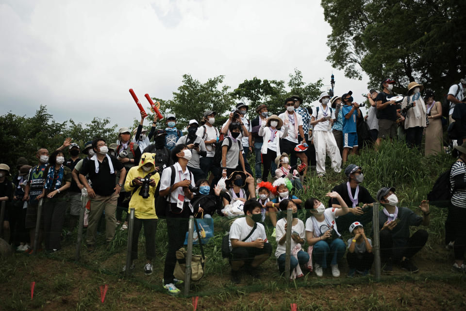 Masked fans watch from a hillside during the men's cross country mountain bike competition at the 2020 Summer Olympics, Monday, July 26, 2021, in Izu, Japan. (AP Photo/Thibault Camus)