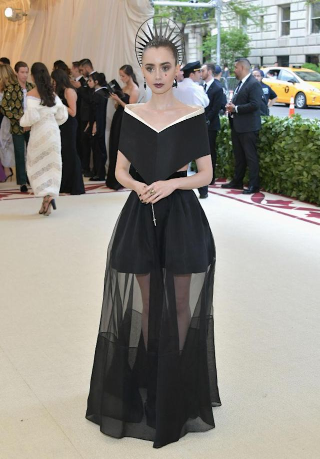 <p>Collins went to the dark side in a sheer black Givenchy dress, and accessorized with some rosary beads in hand. (Photo: Getty Images) </p>
