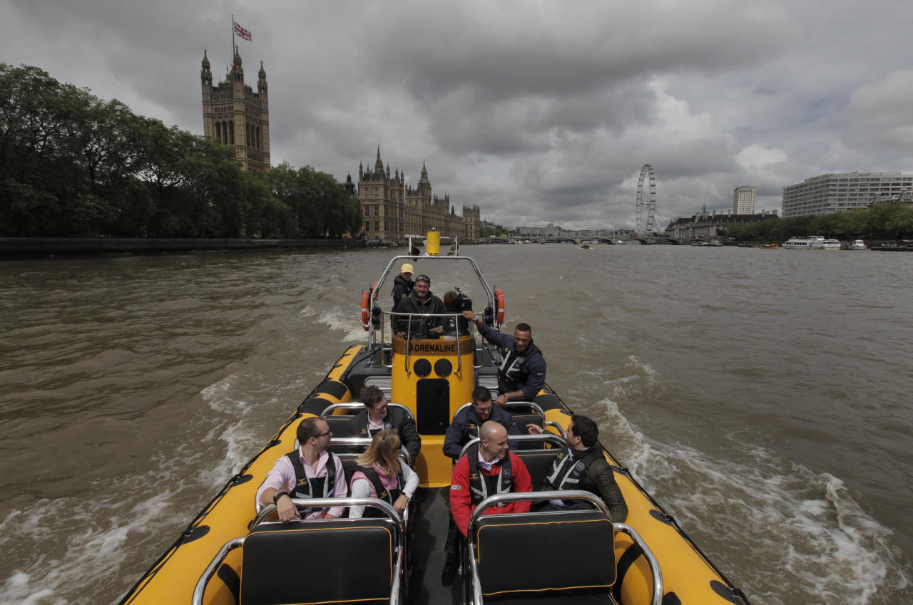 In this Wednesday, July 4, 2012, people are seen aboard a high-speed 12-seater rigid inflatable boat, run by the Protection Services International company as it travels past the Palace of Westminster on London's river Thames. Companies like Protection Services International are just one of the many catering to the super rich who are coming to the London games and demand top security and easy transport. (AP Photo/Lefteris Pitarakis)