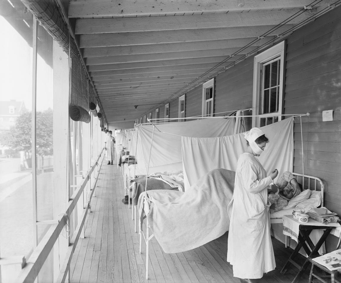 Masked Nurse at the Head of a Row of Beds Treating Patient during Influenza Pandemic, Walter Reed Hospital, Washington DC, USA, Harris & Ewing, 1918. (Photo by: Universal History Archive/Universal Images Group via Getty Images)