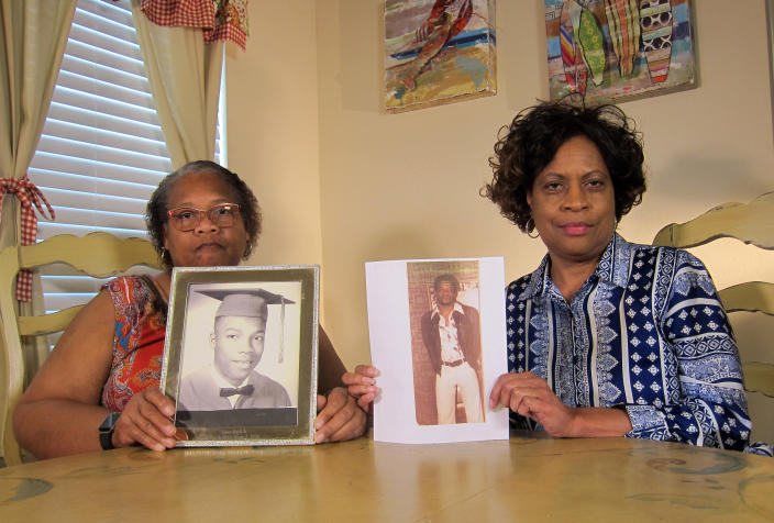 In this Wednesday, April 10, 2019, photo Mylinda Byrd Washington, 66, left, and Louvon Byrd Harris, 61, hold up photographs of their brother James Byrd Jr. in Houston. James Byrd Jr. was the victim of what is considered to be one of the most gruesome hate crime murders in recent Texas history. (AP Photo/Juan Lozano)