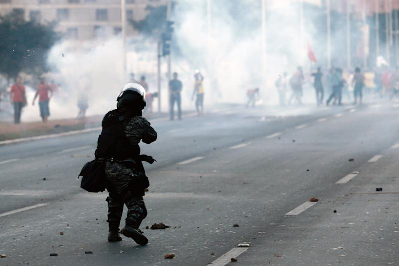 A military police officer fires a tear gas grenade against demonstrators