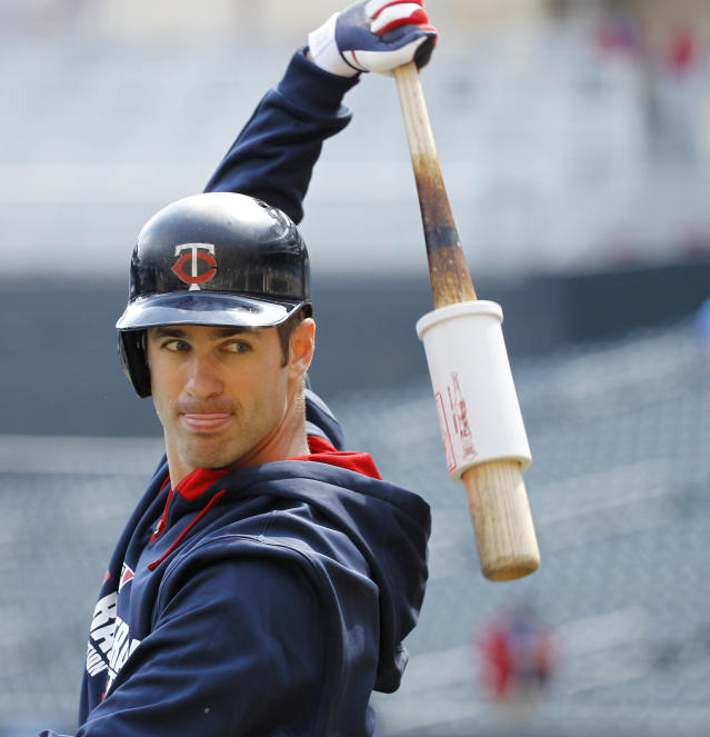 Minnesota Twins first baseman Joe Mauer stretches before the Minnesota Twins host the Oakland Athletics in a home opener baseball game in Minneapolis, Monday, April 7, 2014. (AP Photo/Ann Heisenfelt)