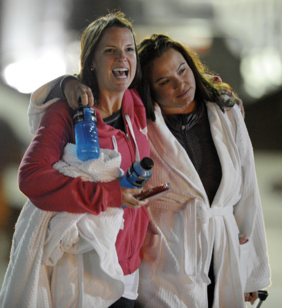 Kristina Courson, left, of Paris, Texas, is embraced by Jamie Hilliard, of Denison, Texas, after getting off the cruise ship Carnival Triumph in Mobile, Ala., Thursday, Feb. 14, 2013. The ship with more than 4,200 passengers and crew members has been idled for nearly a week in the Gulf of Mexico following an engine room fire. (AP Photo/G M Andrews)