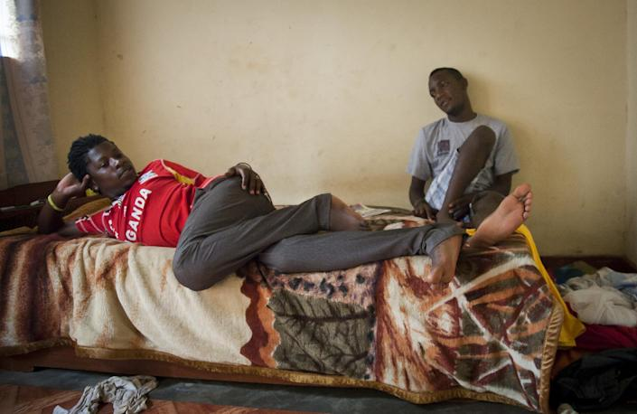 """In this photo taken Saturday, March 22, 2014, two Ugandan homosexuals sit in the one-room safe-house where they now live, at an undisclosed location in Uganda. The enactment of Uganda's new anti-gay law has spread fear among homosexuals, forcing many to flee to so-called """"safe houses"""", often single rooms that are more likely to be locked up day and night because of safety concerns. (AP Photo)"""