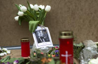A portrait of Britain's Prince Philip is placed with flowers and candles in front of the British embassy in Berlin, Germany, Saturday, April 10, 2021. Britain's Prince Philip, husband of Queen Elizabeth II, who spent more than seven decades supporting his wife in a role that mostly defined his life, died on Friday. (AP Photo/Markus Schreiber)