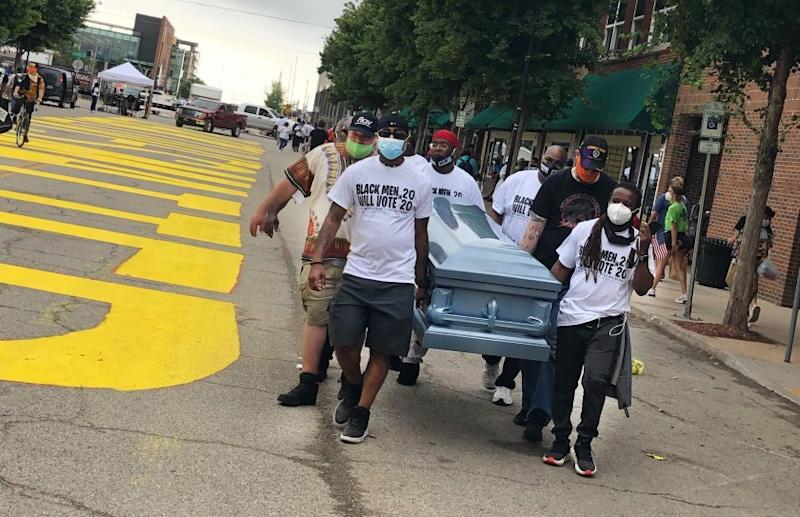 """Volunteers from a Dallas-based non-profit carry an empty coffin past a new Black Lives Matter sign painted on Greenwood Avenue for Juneteenth. The mens' leader, Bruce Carter, said they were sending a message with the coffin: """"We should all receive justice."""""""