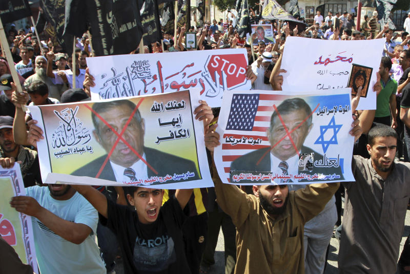 "FILE - In this Friday, Sept. 14, 2012 file photo, Palestinian Islamic Jihad supporters rally with banners depicting Morris Sadek during a protest in Khan Younis, southern Gaza Strip, as part of widespread anger across the Muslim world about a film ridiculing Islam's Prophet Muhammad. The banners in Arabic read, ""Death to Israel,"" ""death to America"" and, ""anyone but God's Prophet."" An Egyptian court on Wednesday, Nov. 28, 2012 has convicted in absentia seven Egyptian Coptic Christians and a Florida-based American pastor and sentenced them to death on charges linked to an anti-Islam film that had sparked riots in parts of the Muslim world. (AP Photo/Adel Hana, File)"
