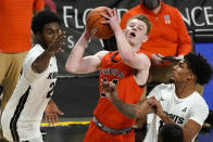 Auburn guard Justin Powell, center, shoots as he gets between Central Florida guard Dre Fuller Jr., left, and guard Brandon Mahan, right, during the second half of an NCAA college basketball game, Monday, Nov. 30, 2020, in Orlando, Fla. (AP Photo/John Raoux)