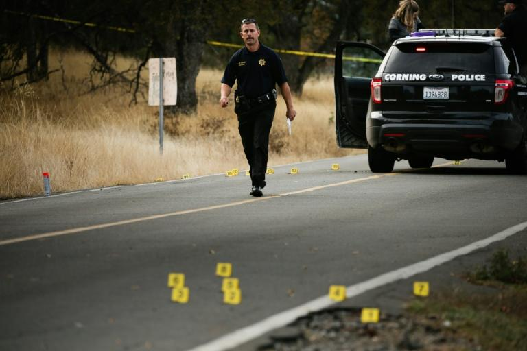A law enforcement officer is seen at one of many crime scenes after the shooting