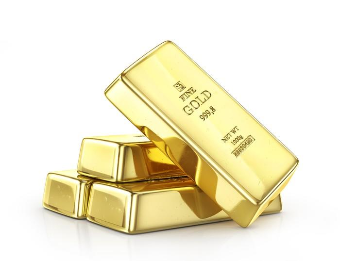 A gold bar leaning half up on three gold bars sitting on a surface.