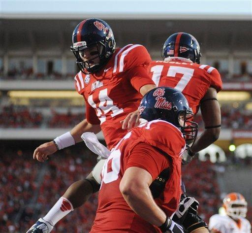 Mississippi quarterback Bo Wallace (14) celebrates his touchdown run with teammates Mississippi tight end Jamal Mosley (17) and Mississippi center Evan Swindall (56) against UTEP during an NCAA college football game at Vaught-Hemingway Stadium in Oxford, Miss., Saturday, Sept. 8, 2012. (AP Photo/Oxford Eagle, Bruce Newman) MAGAZINES OUT; NO SALES; MANDATORY CREDIT