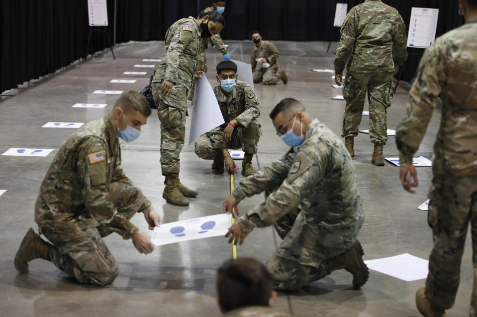 Members of the Nevada National Guard install social distancing stickers while setting up a new temporary coronavirus testing site Monday, Aug. 3, 2020, in Las Vegas. (AP Photo/John Locher)