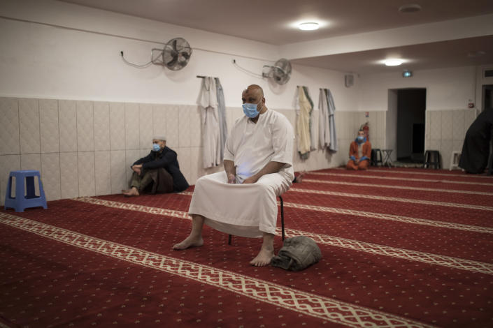 A man wearing a mask practices social distancing while praying at the Tahara Mosque during the coronavirus pandemic in Marseille, at a closed door radio broadcast of the Friday prayers to confined worshippers at home, in southern France, April 24, 2020, on the first day of Ramadan. (AP Photo/Daniel Cole)