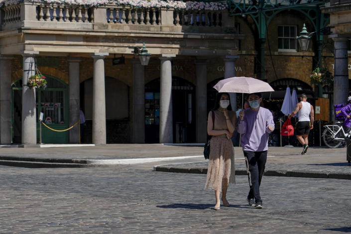 A couple wear face masks as they shelter from the sun under an umbrella, while they walk in Covent Garden, in London, Monday, June 14, 2021. British Prime Minister Boris Johnson is expected to confirm Monday that the next planned relaxation of coronavirus restrictions in England will be delayed as a result of the spread of the delta variant first identified in India. (AP Photo/Alberto Pezzali)