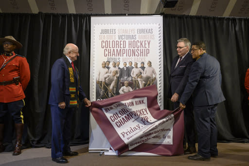 From left, Arthur J. LeBlanc, Lt. Gov. of Nova Scotia, Doug Ettinger, President and CEO of Canada Post, and Craig Smith, President of The Black Cultural Society, unveil Canada Post's stamp honouring the Colored Hockey Championship and the all-Black hockey teams in the Maritimes between 1895 and the early 1930s during an event at the Black Cultural Center in Halifax, Nova Scotia, Thursday, Jan. 23, 2020. (Darren Calabrese/The Canadian Press via AP)