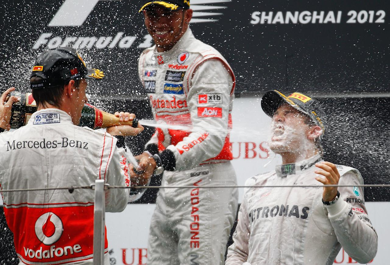 SHANGHAI, CHINA - APRIL 15:  Race winner Nico Rosberg (R) of Germany and Mercedes GP celebrates with second placed Jenson Button (L) of Great Britain and McLaren and third placed Lewis Hamilton (C) of Great Britain and McLaren on the podium following the Chinese Formula One Grand Prix at the Shanghai International Circuit on April 15, 2012 in Shanghai, China.  (Photo by Paul Gilham/Getty Images)