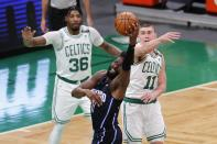 Orlando Magic's James Ennis III, center, struggles to control the ball against Boston Celtics' Payton Pritchard (11) and Marcus Smart (36) during the first half on an NBA basketball game, Sunday, March 21, 2021, in Boston. (AP Photo/Michael Dwyer)