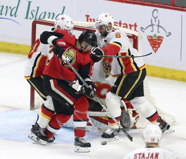 Calgary Flames center Curtis Lazar (20) and defenseman Mark Giordano (5) check Ottawa Senators right wing Alexandre Burrows (14) in front of the Flames net during the second period of an NHL hockey game in Ottawa, Friday, March 9 2018. (Fred Chartrand/The Canadian Press via AP)