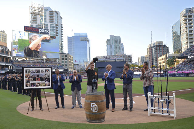 San Francisco Giants' Bruce Bochy, center, acknowledges the crowd during a retirement ceremony in his honor before a baseball game against the San Diego Padres, Friday, July 26, 2019, in San Diego. Bochy will retire at the end of the season and is playing his last regular season series in San Diego. (AP Photo/Orlando Ramirez)