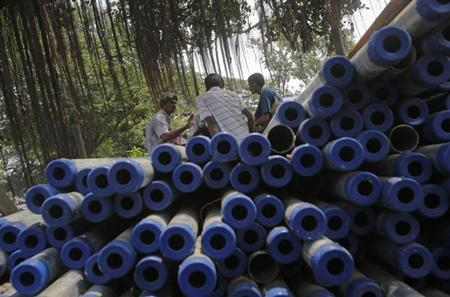 Workers sit on iron pipes before loading them on a truck at an iron and steel market in an industrial area in Mumbai September 11, 2013. REUTERS/Danish Siddiqui/Files